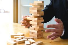 Επιχειρηματίες που επιλέγουν dominoe τους φραγμούς για να γεμίσει τα ελλείποντα ντόμινο α στοκ εικόνα