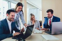Επιχειρηματίες που εργάζονται στο στην αρχή χρησιμοποιώντας lap-top επιχειρησιακού προγράμματος στοκ εικόνες