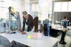 Επιχειρηματίες που εργάζονται στο φορητό προσωπικό υπολογιστή στην αρχή στοκ εικόνα με δικαίωμα ελεύθερης χρήσης