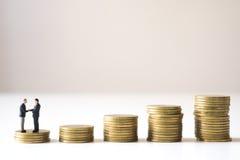 Επιχειρηματίες που ελέγχουν το χέρι στο πρώτο βήμα του σκαλοπατιού σωρών νομισμάτων Στοκ Εικόνες