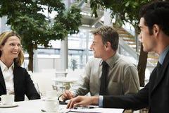 Επιχειρηματίες που διοργανώνουν μια συζήτηση στον καφέ γραφείων Στοκ εικόνες με δικαίωμα ελεύθερης χρήσης