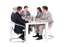 Επιχειρηματίες που διοργανώνουν τη συνεδρίαση των διασκέψεων πέρα από το άσπρο υπόβαθρο Στοκ Εικόνα