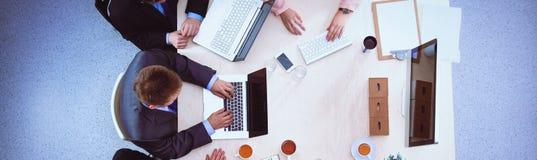 Επιχειρηματίες που κάθονται και που συζητούν στην επιχειρησιακή συνεδρίαση, στην αρχή Στοκ Φωτογραφία