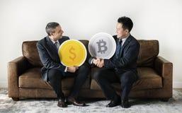 Επιχειρηματίες που κάθονται μαζί με τα εικονίδια νομισμάτων χρημάτων Στοκ φωτογραφία με δικαίωμα ελεύθερης χρήσης