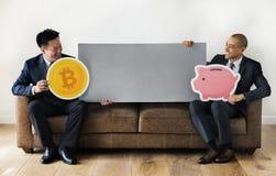 Επιχειρηματίες που κάθονται μαζί με τα εικονίδια χρημάτων Στοκ Εικόνα