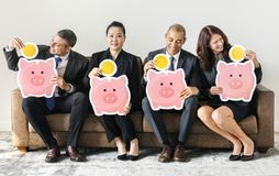 Επιχειρηματίες που κάθονται μαζί με τα piggy εικονίδια τραπεζών Στοκ Φωτογραφία
