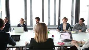 Επιχειρηματίες που κάθονται στον πίνακα στην παρουσίαση αίθουσας συνδιαλέξεων και ακούσματος απόθεμα βίντεο
