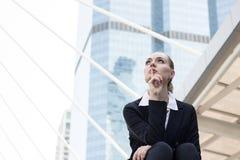 Επιχειρηματίες που κάθονται στο σκαλοπάτι έξω από την οικοδόμηση και τη σκέψη και στοκ εικόνα