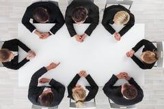 Επιχειρηματίες που κάθονται τον κενό πίνακα Στοκ Εικόνα
