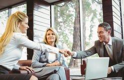 Επιχειρηματίες που κάνουν μια διαπραγμάτευση σε μια συνεδρίαση Στοκ Φωτογραφία
