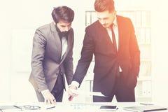 Επιχειρηματίες που κάνουν τη γραφική εργασία από κοινού Στοκ Εικόνα