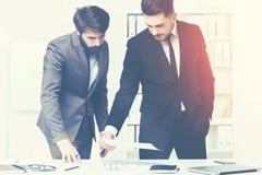 Επιχειρηματίες που κάνουν τη γραφική εργασία στην αρχή Στοκ εικόνα με δικαίωμα ελεύθερης χρήσης