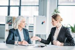 Επιχειρηματίες που και που συζητούν το επιχειρησιακό πρόγραμμα για τη συνάντηση στην αρχή Στοκ εικόνα με δικαίωμα ελεύθερης χρήσης