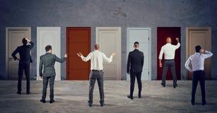 Επιχειρηματίες που κοιτάζουν για να επιλέξει τη σωστή πόρτα Έννοια της σύγχυσης και του ανταγωνισμού στοκ εικόνες με δικαίωμα ελεύθερης χρήσης