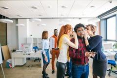Επιχειρηματίες που κουτσομπολεύουν για τους συναδέλφους στην αρχή Στοκ Εικόνες