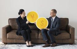 Επιχειρηματίες που κρατούν τα εικονίδια νομίσματος Στοκ φωτογραφίες με δικαίωμα ελεύθερης χρήσης