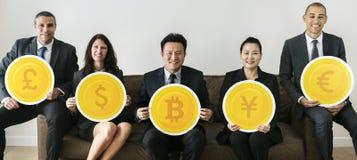 Επιχειρηματίες που κρατούν τα εικονίδια νομίσματος Στοκ Εικόνα