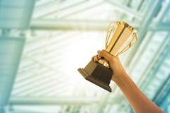 Επιχειρηματίες που κρατούν το βραβείο τροπαίων στοκ εικόνες