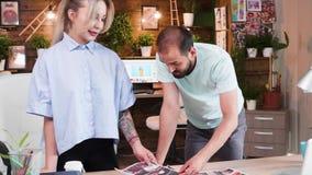 Επιχειρηματίες που μιλούν για τις ιδέες των διευθυντών τέχνης τους στο γραφείο τους φιλμ μικρού μήκους