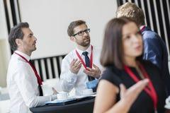 Επιχειρηματίες που μιλούν κατά τη διάρκεια του διαλείμματος στο κέντρο συμβάσεων Στοκ Εικόνες