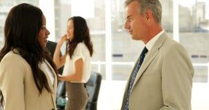 Επιχειρηματίες που μιλούν μαζί και χέρια τινάγματος φιλμ μικρού μήκους