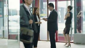 Επιχειρηματίες που μιλούν στην αίθουσα ανελκυστήρων απόθεμα βίντεο