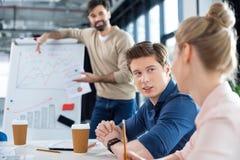 Επιχειρηματίες που μιλούν στον πίνακα στη μικρή συνεδρίαση των γραφείων Στοκ εικόνες με δικαίωμα ελεύθερης χρήσης