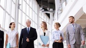 Επιχειρηματίες που περπατούν κατά μήκος του κτιρίου γραφείων 4 απόθεμα βίντεο