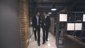 Επιχειρηματίες που περπατούν μέσω του διαδρόμου και της ομιλίας φιλμ μικρού μήκους