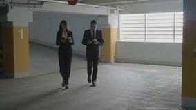 Επιχειρηματίες που περπατούν σε έναν υπόγειο χώρο στάθμευσης κρατώντας τον καφέ στα χέρια τους και εξετάζοντας τα smartphones του απόθεμα βίντεο