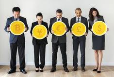 Επιχειρηματίες που στέκονται και που κρατούν τα εικονίδια νομίσματος Στοκ Εικόνα
