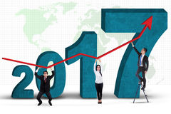 Επιχειρηματίες που στέκονται με τους αριθμούς 2017 και τη γραφική παράσταση Στοκ φωτογραφία με δικαίωμα ελεύθερης χρήσης