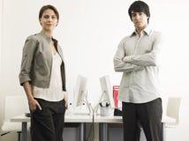 Επιχειρηματίες που στέκονται στα γραφεία υπολογιστών στοκ φωτογραφία