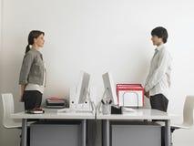 Επιχειρηματίες που στέκονται στα γραφεία υπολογιστών Στοκ Φωτογραφίες