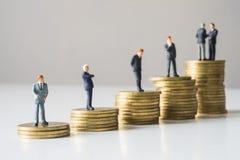 Επιχειρηματίες που στέκονται στο σωρό νομισμάτων Στοκ φωτογραφία με δικαίωμα ελεύθερης χρήσης