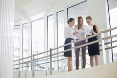 Επιχειρηματίες που συζητούν πέρα από τη γραφική εργασία ενάντια στο κιγκλίδωμα Στοκ Εικόνα