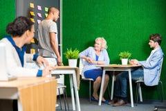 Επιχειρηματίες που συζητούν στο σύγχρονο λόμπι γραφείων Στοκ Φωτογραφίες
