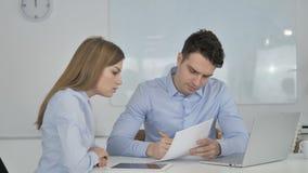 Επιχειρηματίες που συζητούν τα έγγραφα σχετικά με το πρόγραμμα, γραφική εργασία φιλμ μικρού μήκους