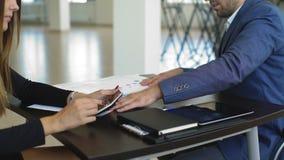 Επιχειρηματίες που συζητούν τα διαγράμματα και τις γραφικές παραστάσεις που παρουσιάζουν τα αποτελέσματα της επιτυχούς ομαδικής ε φιλμ μικρού μήκους