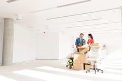 Επιχειρηματίες που συζητούν υπερασπιμένος τα κουτιά από χαρτόνι στο νέο γραφείο Στοκ Φωτογραφία