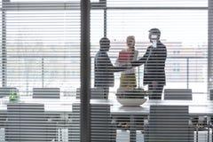 Επιχειρηματίες που τινάζουν τα χέρια από τη γυναίκα συνάδελφοι στο δωμάτιο πινάκων που βλέπει μέσω του παραθύρου γριλληών παραθύρ Στοκ Φωτογραφία