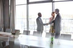 Επιχειρηματίες που τινάζουν τα χέρια από τη γυναίκα συνάδελφος στη αίθουσα συνδιαλέξεων στο γραφείο Στοκ Φωτογραφίες