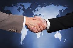 Επιχειρηματίες που τινάζουν τα χέρια ενάντια στο worldmap Στοκ Φωτογραφίες