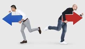 Επιχειρηματίες που τρέχουν στις διαφορετικές κατευθύνσεις στοκ εικόνες