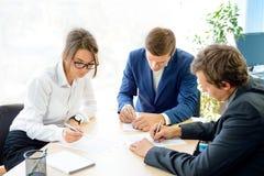 Επιχειρηματίες που υπογράφουν τη σύμβαση γύρω από τον πίνακα στο σύγχρονο γραφείο Έννοια επιχειρησιακής συνεργασίας Στοκ εικόνα με δικαίωμα ελεύθερης χρήσης