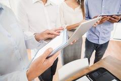 Επιχειρηματίες που χρησιμοποιούν διάφορες ηλεκτρονικές συσκευές Στοκ εικόνα με δικαίωμα ελεύθερης χρήσης