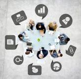 Επιχειρηματίες σε μια συνεδρίαση με τα επιχειρησιακά σύμβολα Στοκ Εικόνα