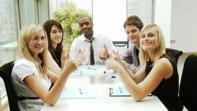 Επιχειρηματίες σε μια συνεδρίαση με τους αντίχειρες επάνω φιλμ μικρού μήκους