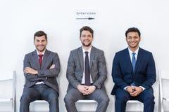 Επιχειρηματίες στα κοστούμια που κάθονται στις καρέκλες στην άσπρη αίθουσα αναμονής στοκ φωτογραφία