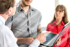 Επιχειρηματίες στη συνεδρίαση που εργάζεται στο lap-top, επίδραση ελαφριών ακτίνων Στοκ Φωτογραφία